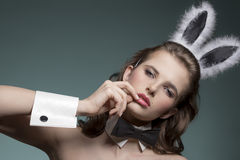 Sexy girl with bunny ears. Close-up easter portrait of sexy brunette girl with fluffy bunny ears and black papillon, looking in camera Royalty Free Stock Photography
