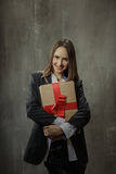 Sexy girl in classic jacket and shirt with a gift in the hands s Royalty Free Stock Image