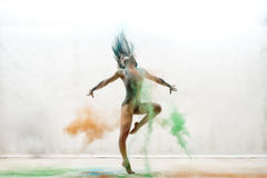 Sexy girl in a cloud of color dust studio portrait Royalty Free Stock Images