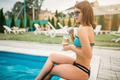 Sexy girl with cocktail sitting by the poolside Stock Photo