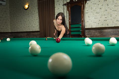 Sexy girl in corset plays billiards. Stock Image