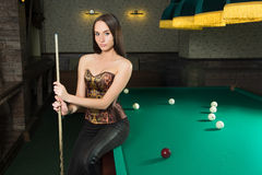 Sexy girl in corset plays billiards. Royalty Free Stock Images