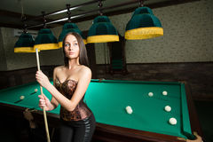 Sexy girl in corset plays billiards. Royalty Free Stock Image