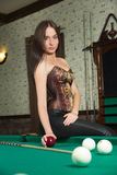 Sexy girl in corset plays billiards. Royalty Free Stock Photography