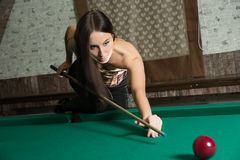 Sexy girl in corset plays billiards. Stock Photos