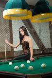 Sexy girl in corset plays billiards. Stock Photos