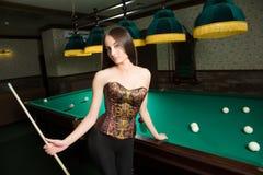 girl in corset plays billiards. Stock Photos
