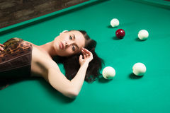 Sexy girl in corset plays billiards. Royalty Free Stock Photo