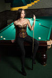 Sexy girl in corset plays billiards. Stock Photo