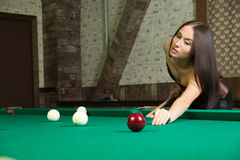 Sexy girl in corset plays billiards. Stock Images