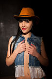 Girl in cowboy hat and jeans. On a black background Royalty Free Stock Images