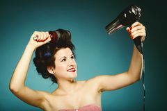 Sexy girl in curlers with hairdryer styling hair Royalty Free Stock Photo