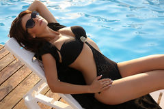 Sexy girl with dark hair in black swimsuit and sunglasses Royalty Free Stock Photos