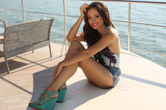 Sexy girl with dark hair in elegant swimsuit relaxing on yacht. Fashion outdoor photo of beautiful sexy girl with dark hair in elegant swimsuit and jeans shorts Stock Photography