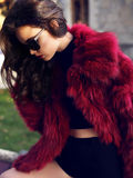 Sexy girl with dark hair in fashion red fur coat and sunglasses Stock Image