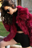 Sexy girl with dark hair in fashion red fur coat and sunglasses Stock Photo