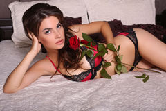 Sexy girl with dark hair in lingerie lying on bed Royalty Free Stock Photos