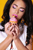 Sexy girl with dark hair and tanned skin, holding delicious cake Royalty Free Stock Image