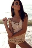 Sexy girl with dark hair and tanned skin posing on beach Stock Photos