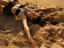 girl with dark hair and tanned skin posing on beach Stock Images