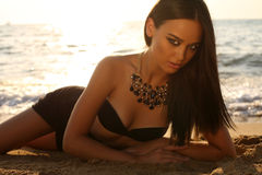 Sexy girl with dark hair and tanned skin posing on beach Royalty Free Stock Image