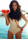 girl with dark hair with watermelone beside a swimming pool Royalty Free Stock Photos
