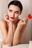 Sexy girl with dark hair wears elegant lace lingerie, holding red heart Royalty Free Stock Images