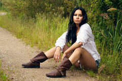 Sexy girl in denim shorts and white shirt. Sitting by the countryside road Stock Photo