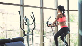 girl doing exercise with exercise bike in the gym. Look behind her stock video footage