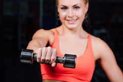 Sexy girl doing exercises in her arms biceps and triceps. fitness with dumbbells in the gym. Nice cute female Stock Photos