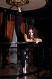 Sexy girl doing split on pole dance Stock Photo