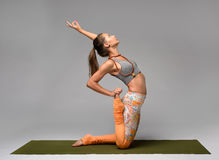 Sexy girl doing yoga. Sexy woman doing yoga in camel pose in studio. Gray background Stock Photos