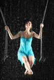 girl in dress riding on swing hold for chain Royalty Free Stock Photos