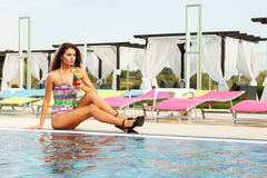Sexy girl drinking cocktail in summer season. Beautiful sexy brunette girl sitting on pool edge with fresh cocktail drink Stock Image