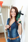 Sexy girl in dungarees with drill Royalty Free Stock Photo