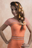 Sexy girl with easter hair-style. Lovely brunette woman in sexy pose with orange spring dress and some easter colorful eggs in her hair-style. Smiling and Stock Image