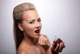 girl eat cherry look at camera Stock Image