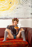 Sexy girl eating spaghetti on the couch Royalty Free Stock Photography