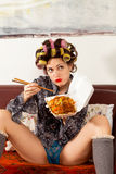 Sexy girl eating spaghetti on the couch Stock Image