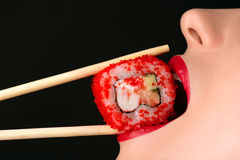 Sexy girl eating sushi roll, sensual red lips. Closeup Royalty Free Stock Photo