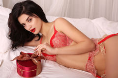 Sexy girl in elegant lace lingerie, holding red heart, symbol of Valentine's day Stock Image
