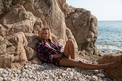 Sexy Girl in flannel shirt on the rocky beach Stock Images