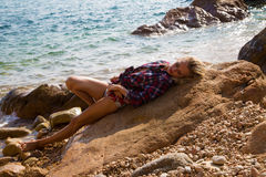 Sexy Girl in flannel shirt on the rocky beach Royalty Free Stock Images