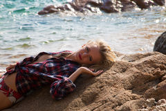 Sexy Girl in flannel shirt on the rocky beach Stock Photos