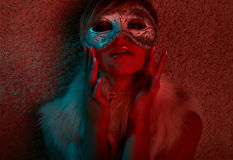 Sexy girl in fur jacket wearing mask Royalty Free Stock Images
