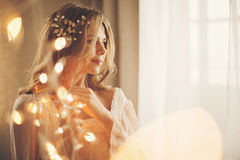Sexy girl with garland. Young lovely housewife with a garland. Girl in sexy gown. Good morning. Dreamy face. Soft focus. Toning Royalty Free Stock Photo