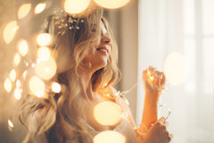 Girl with garland. Young lovely housewife with a garland. Girl in gown. Good morning. Dreamy face. Soft focus. Toning. Creative bokeh royalty free stock images