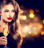 Sexy girl with glass of champagne. Over holiday background Royalty Free Stock Images