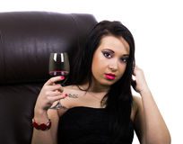 Sexy girl with a glass of wine. Young sexy brunette with a glass of wine sitting on the couch. White background Stock Image