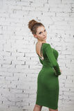 Sexy girl in green dress over brick background Royalty Free Stock Image